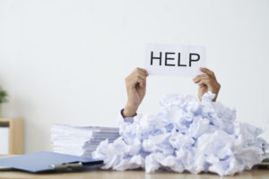 Person under heap of crumpled papers with hand holding a help sign