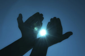 Silhouette of hands holding a bright bluest light from the sun, with the blue sky background.